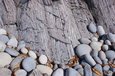 The combination of round and striped rocks on the sea shore.