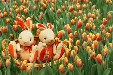 Toy rabbits in the basket among the tulips.