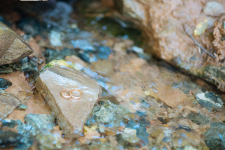 under heart: Wedding rings on the heart shaped rock under clear water Stock Photo