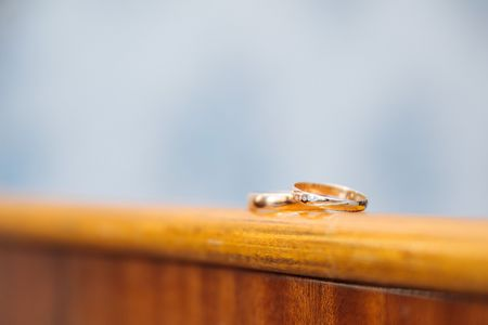 positioned: Gold wedding rings positioned on wooden table Stock Photo