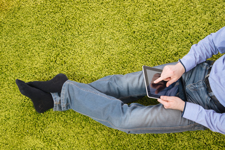 green carpet: young man sitting on a green carpet with tablet