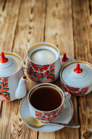 fireclay: tea mug with red ornaments and a teapot on old wooden table
