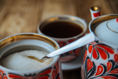fireclay: tea mug with red ornaments on old wooden table Stock Photo