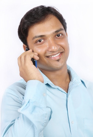 Smiling Indian businessman talking on cellphone photo