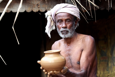 Indian Potter Showing a Pot Which He Made Just Now photo