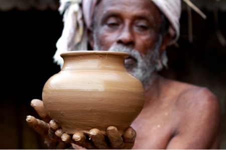 Indian Potter Showing a Pot photo