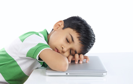 personas tristes: School Boy Sleeping over the laptop Foto de archivo