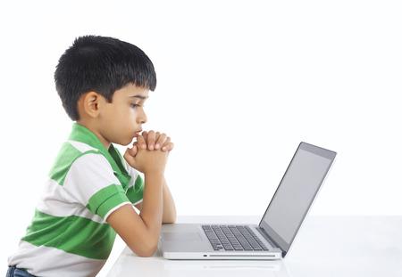 Indian Boy Praying with Laptop Imagens