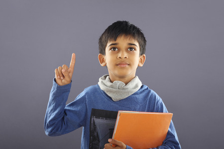 textbook: Portrait of Indian School Boy with Textbook Stock Photo