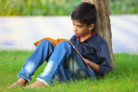Portrait of Indian little boy reading the book, Sitting on green grass in park