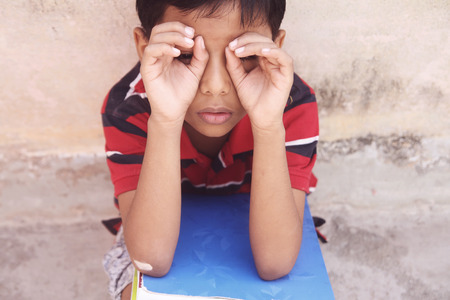 Indian Little boy looking at somewhere through fingers Stock Photo