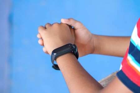 Indian boy wearing smartwatch in his hand Archivio Fotografico