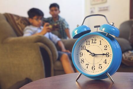 Indian young friends playing video games and alarm clock infront of him