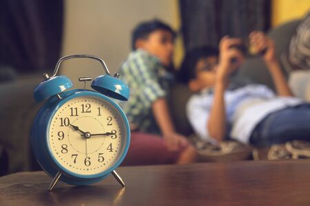 Indian Friends playing video game on smart phone. Alarm-clock is in front of them