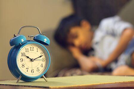 Indian young boy sleeping with alarm clock