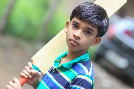 Portrait of Indian boy playing cricket