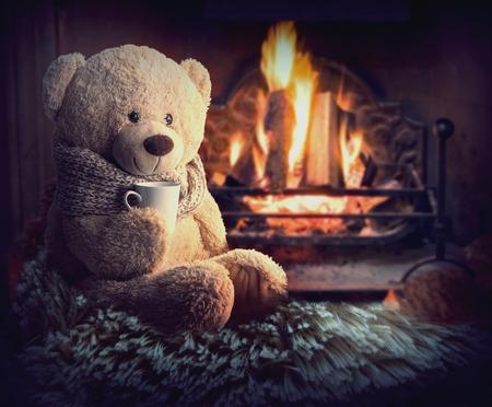 Een teddybeer zit bij de open haard met een kop. huislijkheid Stockfoto