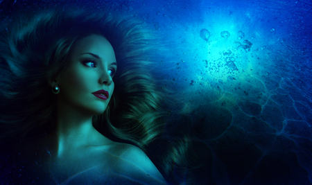 Beautiful girl with long hair in the image of a mermaid under the water Imagens