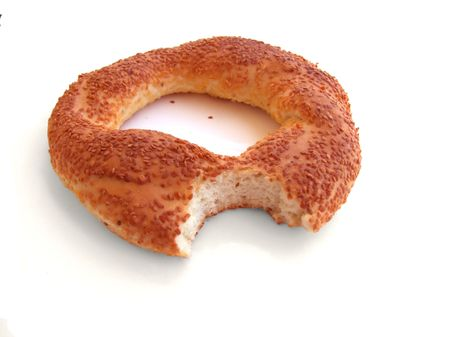 bitten: Bitten bagel with sesame isolated on white
