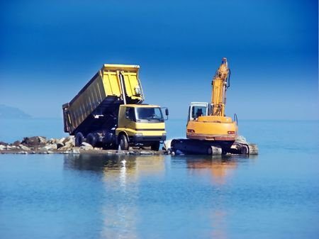 Excavator and dumper working in the sea photo