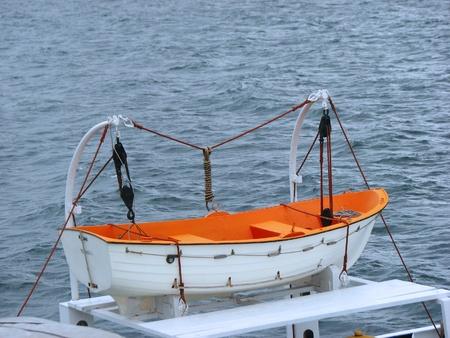 lifeboat: White orange lifeboat on a ferry through the sea