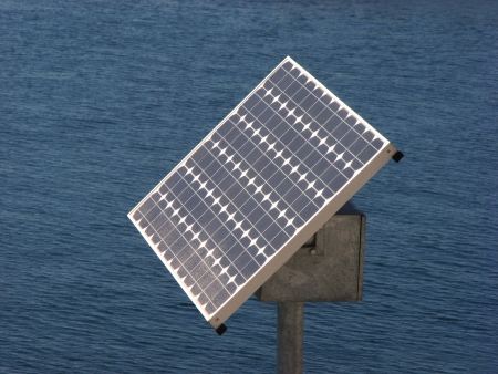 Solar Power Panel on Post against Sea photo