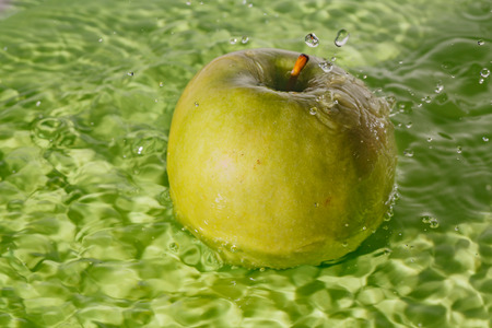 Green apple water splashes during cleaning on green plate.