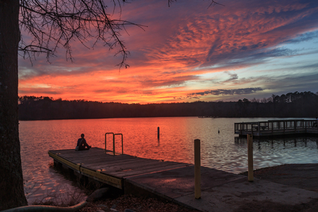 Lonely girl sitting on pier in lake Raleigh in Raleigh, NC during sunset. Archivio Fotografico