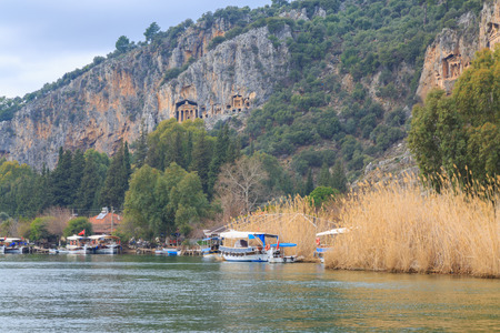 Dalyan river with boats and kings tombs. Stok Fotoğraf