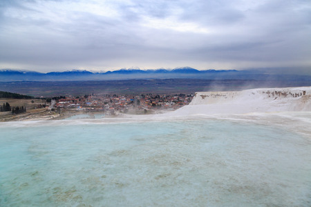 Pamukkale travertines with vapor with moutains bakcground in winter