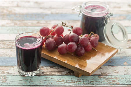 Fresh grape juice (compote) and grapes on vintage table
