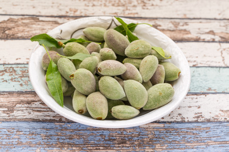 Fresh green unripe almonds on white plate in vintage table Stock Photo