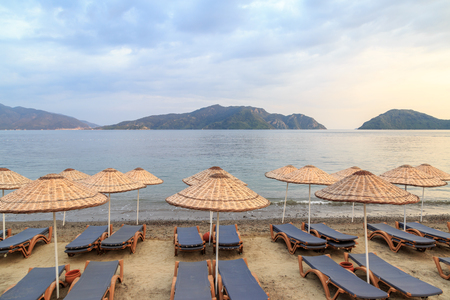 Sunbeds in marmaris beach with mountain view Stock Photo