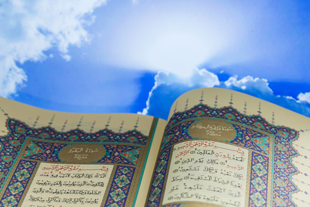 Opening pages of holy book Quran with clouds