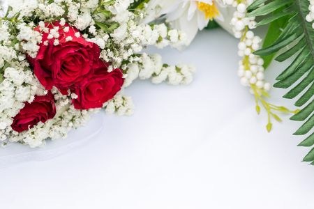White flowers with red roses decors on white table Stock Photo