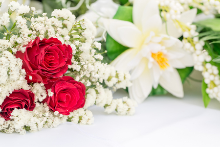 White flowers with red roses decors on white table Standard-Bild