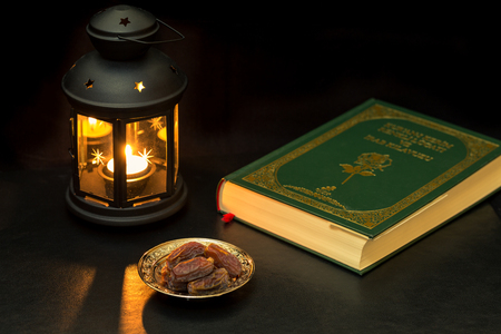 Dates, quran, and lantern at dark Stock Photo