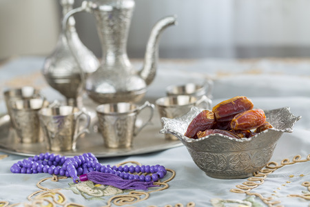 Dates with zam zam water cups background with purple rosary on white table cloth