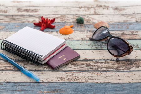 Travel concept: passport, sunglasses, notebook, and seashells side view