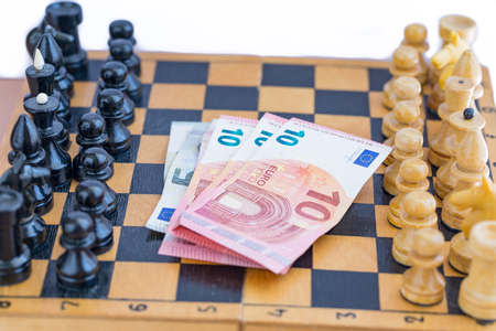 Chess components and money between them Stock Photo