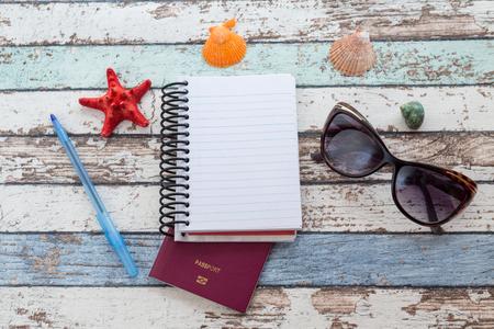 Travel concept: passport, sunglasses, notebook, and seashells top view