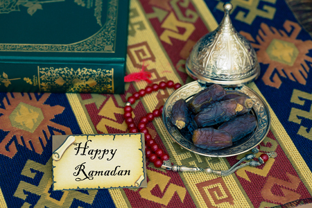 Happy ramadan text on card with dates and Quran