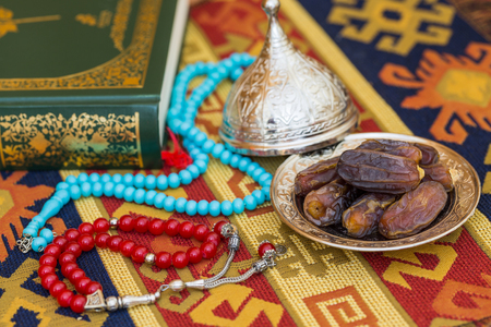 Red and turquoise rosaries, dates, and quran on carpet Stock Photo