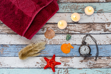 Spa time in summer: Summer spa concept with seashells, towel, candles, and pocket watch Stock Photo