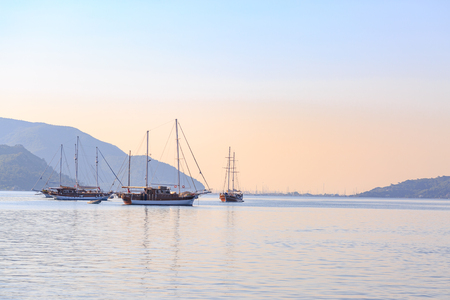 Boat in the sea with mountains background in the morning Stock Photo
