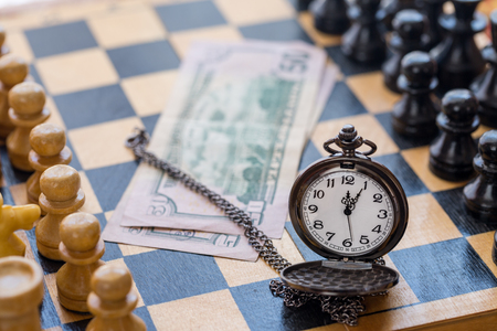 Vintage pocket watch money and chess pieces on chess board