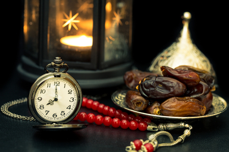 różaniec: Ramadan concept with dates, pocket watch, rosary and lantern in darkness