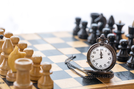 Vintage pocket watch and chess pieces on chess board