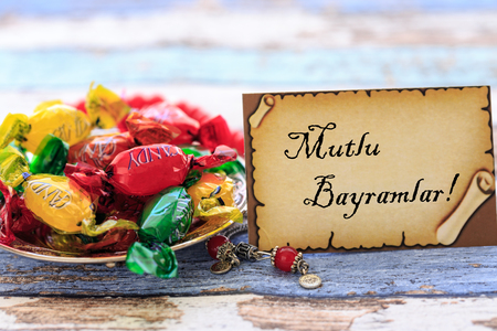 Eid mubarak in turkish on the card with colorful candies on vintage table