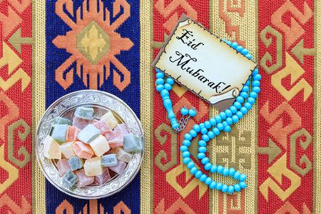 Eid mubarak text on the card with blue rosary and turkish delights on carpet Stok Fotoğraf